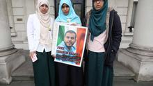 Somaia Halawa, Omaima Halawa and Fatima Halawa  hold a picture in support of their brother Ibrahim who is in prison awaiting trial in Egypt