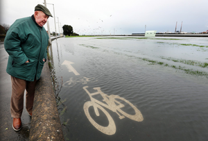 Billy Bradshaw from Clontarf takes a close look at the flooded cycle lane on the coast road