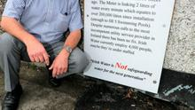 Paul Kealy (lt) the leaking water meter, outside his home at Howth Road, Killester yesterday.