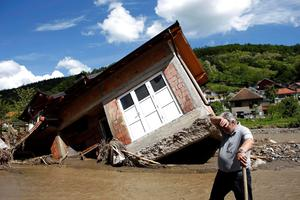 A man reacts near a house tilted by floods in the village of Krupanj, west from Belgrade. Photo: Reuters