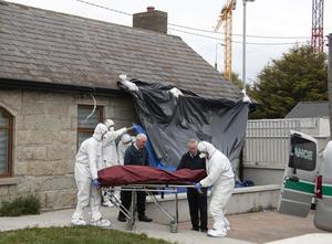 The remains of Alan Hall are removed by gardai after firefighters, attending a blaze at the property, found him dead in the bathroom of his home having suffered injuries to his head and neck. Photo: Colin Keegan/Collins Dublin