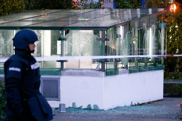 A police officer patrols in front of an entrance of a car parking with broken glasses after a shooting, in Vienna, Austria,