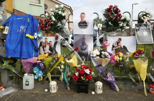 Pictures, candles and floral tributes outside Stephen Lynch's home in Tallaght