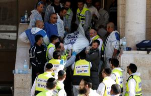 Israeli emergency personnel carry the body of a victim from the scene of an attack at a Jerusalem synagogue November 18, 2014. Two suspected Palestinian men armed with axes and knives killed four people in a Jerusalem synagogue on Tuesday before being shot dead by police, Israeli police and emergency services said, the deadliest such attack in the city in years. REUTERS/Finbarr O'Reilly