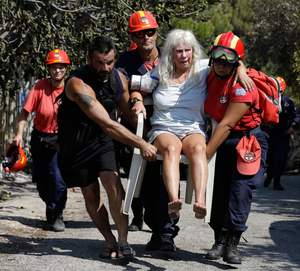 An injured woman is carried to safety in Mati. Photo: AP