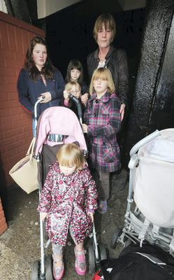 Lisa O'Brien shelters in the stairway of flats at Oliver Bond House with her children Daisy (2), Gypsie (13), Precious (7), Ocean (4) and Chinne (8).
