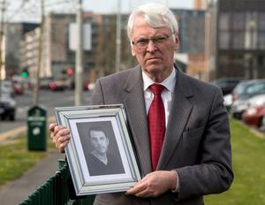 Charlie O'Connor holding a photo of his late son Robert
