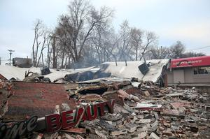 A sign sits amidst rubble at a building that was damaged during a demonstration on November 25, 2014 in Dellwood, Missouri.  Demonstrators caused extensive damage in Ferguson and surrounding areas after a St. Louis County grand jury decided to not indict Ferguson police Officer Darren Wilson in the shooting of Michael Brown