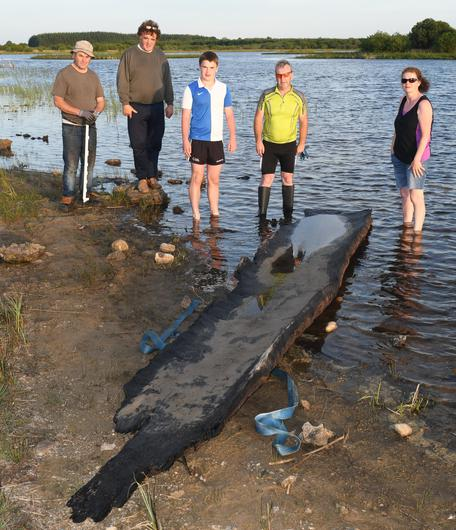 Cathal McDonagh and his family with the five-metre logboat that archaeologists believe could date from 2,000BC
