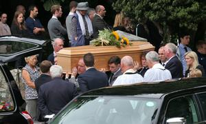 The remains are carried after the funeral service followed by Lorcan Miller's parents, Ken and Sinead, at Rathmichael Church, Dublin this morning