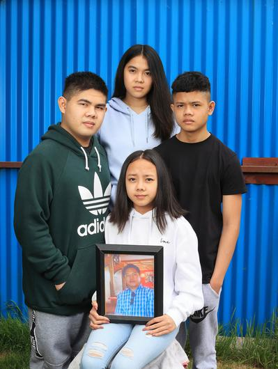 Mikee Plangca and her siblings Chekie, Michael and John hold a photo of their father