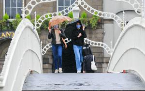 People braving the bad weather on the Ha'penny Bridge. Photo: Gareth Chaney / Collins