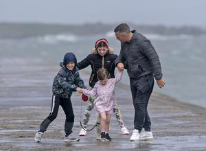 Ken Pearson from Balgriffin battles the wind as he walks on Howth Pier with his children, Holly (10), Callum (7), Ella (3) and their dog Mylo, in the wake of Storm Ellen.