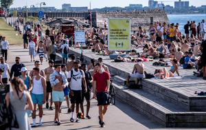 People enjoy the sun without observing social distancing or wearing face masks in Malmo, Sweden, in June