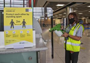 A DAA staff member disinfecting at check-in areas at Dublin Airport