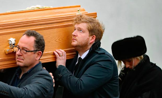 Jack Clarke, the son of Marian Finucane, helps carry her coffin during her funeral in Co Kildare yesterday