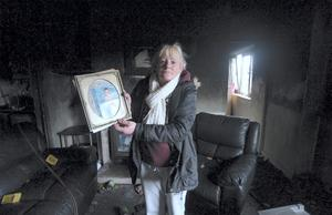 Caroline Fagan (with a picture of her son that she managed to recover) in her burnt-out flat. St. Teresa's Gardens, Donore Avenue, Dublin
