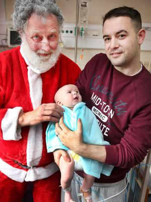 Santa delivers presents to seven-week-old Kai Kelly Knowles and dad James