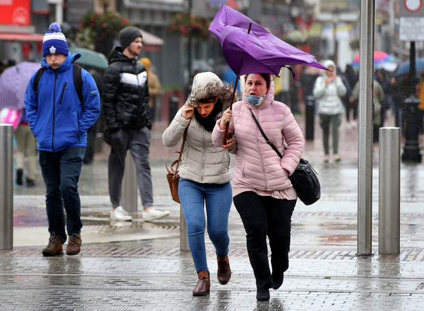 Umbrellas didn't last very long when wind and rain swept O'Connell Street – forecast or not. Photo: Steve Humphreys