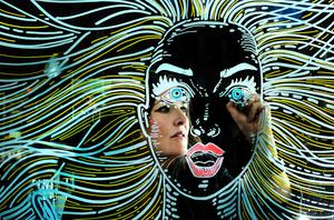 Joanne Murphy works on her 'bad hair day' mural in the window of Ciaran Nevin's salon