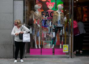 A shopper on Grafton Street in front of a shop window selling colourful masks