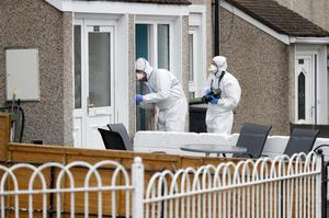 Forensics officers examine blood on the doorframe of the house in Darndale where the couple were stabbed