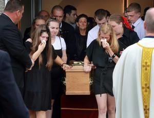 Mourners escort the remains of Aidan McMenamy after his funeral mass at St Joseph's Church in Bonnybrook