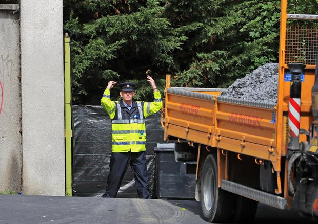 A garda directs a gravel truck at the site of the search in Chapelizod, Dublin, with the area concealed by black canvas. Photo: Colin Keegan/Collins Photo Agency Dublin