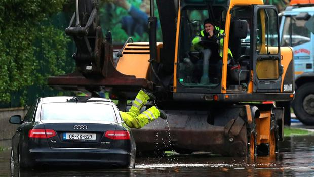 Emergency workers remove a car in the Corbally area of Limerick as flooding continues along the River Shannon