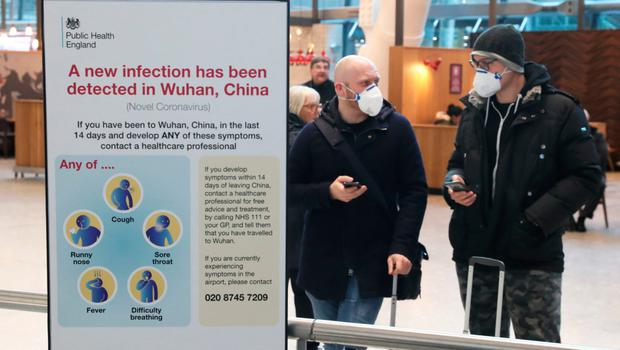 Passengers with face masks at Heathrow Airport in London after the last British Airways flight from China touched down