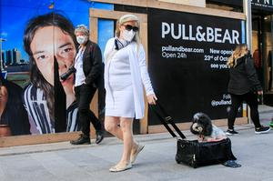 Wearing a face mask, Caroline Malaugh takes her Labradoodle Molly for a walk on Henry Street yesterday
