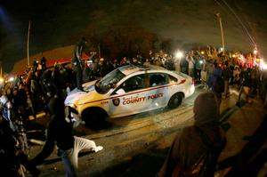 A protester squirts lighter fluid on a police car as the car windows are shattered near the Ferguson Police Department after the announcement of the grand jury decision not to indict police Officer Darren Wilson in the fatal shooting of Michael Brown, an unarmed black 18-year-old, Monday, Nov. 24, 2014, in Ferguson