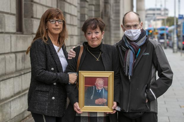 Patrick Dillon's children; (L-R) Caroline Dillon, Ann Walsh, holding the framed photograph of their deceased father, Patrick Dillon, and Gerard Dillon outside the High Court yesterday (MON) after the family settled their case against Beaumont Hospital.