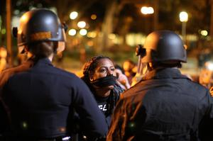 Protesters and police clash in front of LAPD Headquarters as people react to the grand jury decision not to indict a white police officer who had shot dead an unarmed black teenager in Ferguson, Missouri, in the early morning hours of November 25, 2014 in Los Angeles, California. Police officer Darren Wilson shot 18-year-old Michael Brown on August 9, sparking large ongoing protests
