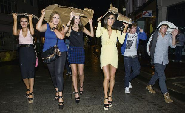A clever group avoid one of the downpours in Grafton Street, which failed to dampen spirits. Photo: Doug O'Connor