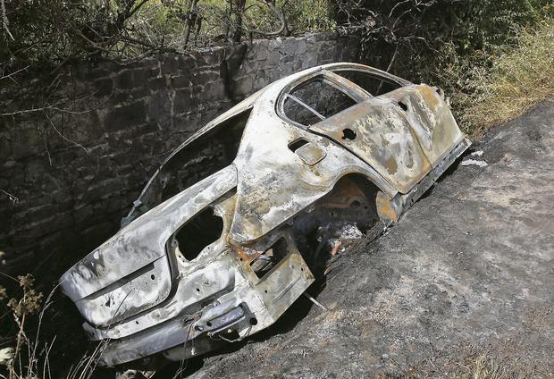 The burnt-out remains of the silver BMW driven by Mauzam Aziz. Photo: Colin Keegan/Collins