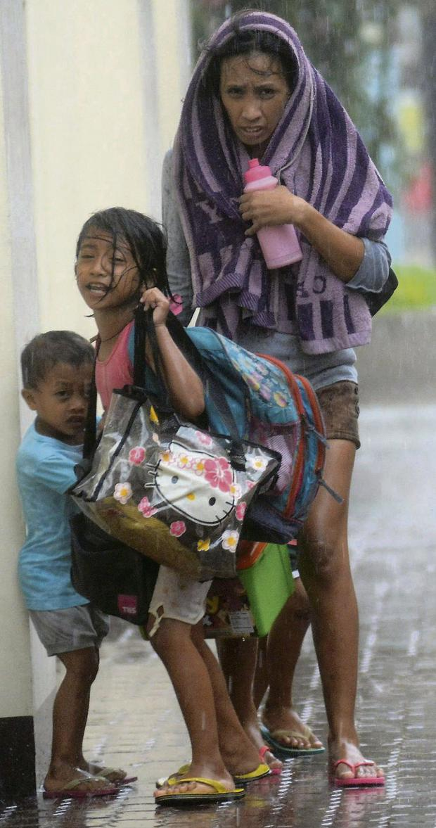 A mother takes refuge with her children as Typhoon Haiyan hits Cebu in the Philippines. Photo: Reuters