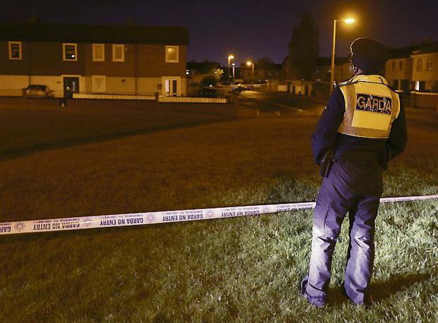 Attack: Gardai seal off the area around Ferrycarrig Park in Coolock where a man in his 20s was shot three times.