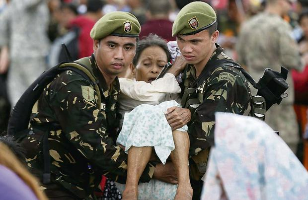 Disaster: Soldiers carry an injured woman. Photo: Reuters