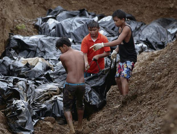 Children carrying body bags. AP Photo/Aaron Favila