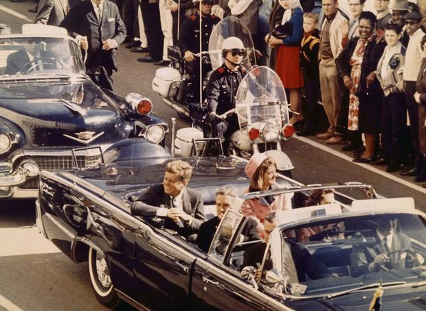 MINUTES FROM DEATH: Kennedy and his wife Jackie ride through Dallas