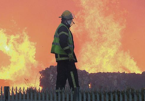 A firefighter tackles the blaze at its height. Photo: Stephen Collins/Collins Photos