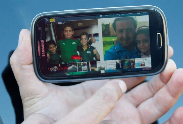 A relative of Lebanese national Manji Hasan holds up his mobile phone displaying a picture of Manji and his children, who the family said were all on board Air Algerie flight AH 5017. Photo: Reuters