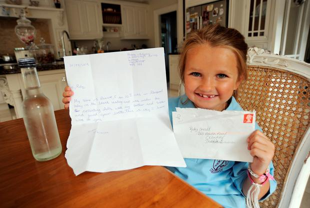 Ruby Small, 7, with the reply letter to her 'message in a bottle' from Rhianne Ridgway, from Manchester, and a similar bottle she used to send her message. Howth road, Dublin