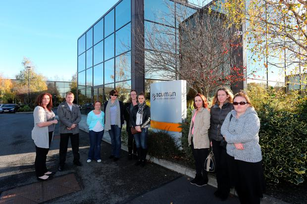 Maria Clarke (lt) and Gosia Vorkowski (rt) pictured with colleagues outside The Acuman Facilities Management offices at Swords Business Campus yesterday.