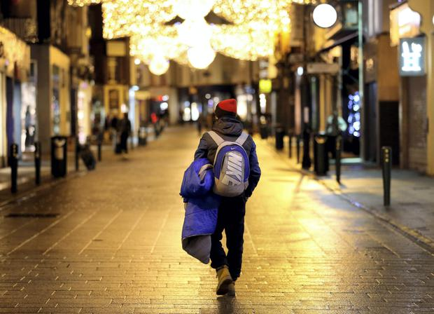 A homeless man makes his way up Dublin's Grafton Street in the early hours, looking for a place to bed down for the night.