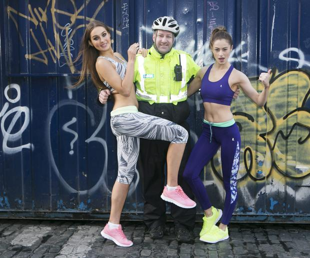 Long arm of law: Models Roz and Madeline pictured with Garda Walsh on yesterday's shoot