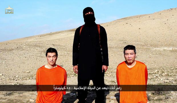 A file image grab taken off a video uploaded on January 20, 2015, reportedly released by the Islamic State (IS) group through Al-Furqan Media, one of the Jihadist platforms used by the militant organisation on the web, allegedly shows Japanese hostages Kenji Goto (L) and Haruna Yukawa (R) in orange jumpsuits with a black-clad militant brandishing a knife as he addresses the camera in English, standing between them at an undisclosed location.