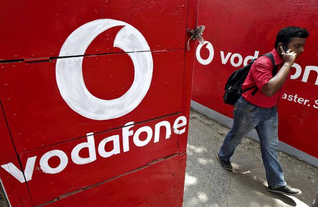 Man speaks on his mobile phone as he walks past the logos of Vodafone