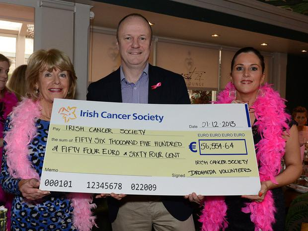 Mark Mellett recieves a cheque on behalf of the Irish Cancer Society from Mary Convery and Grainne Lally Black representing Drogheda Volunteers at the Pink Santa lunch in the Westcourt hotel.